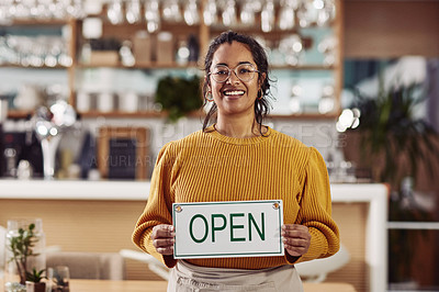 Buy stock photo Cropped shot of a woman holding an open sign while standing in a cafe