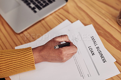 Buy stock photo Cropped shot of a small business owner filling in an application for a loan