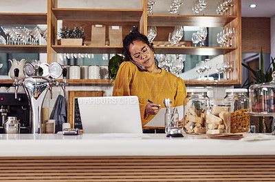 Buy stock photo Shot of a woman talking on the phone while working in a cafe
