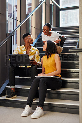Buy stock photo Shot of a group of young businesspeople having a meeting on the stairs of a modern office