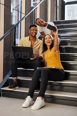 Buy stock photo Shot of a group of young businesspeople taking selfies during a meeting on the stairs of a modern office