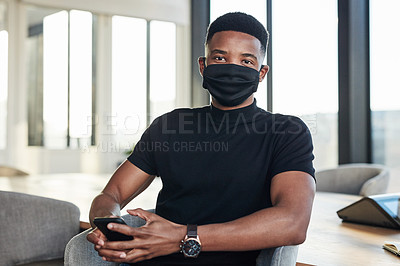 Buy stock photo Shot of a masked young businessman using a smartphone in a modern office
