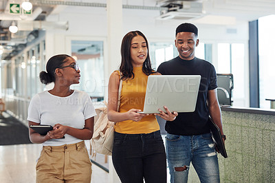 Buy stock photo Shot of a group of young businesspeople using a laptop while walking through a modern office