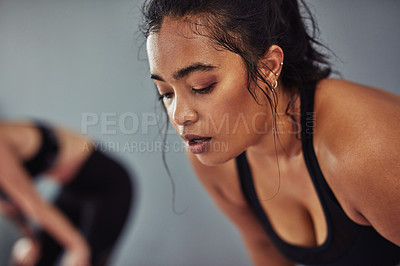 Buy stock photo Shot of a young woman taking a break from her workout at the gym