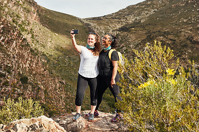 Buy stock photo Shot of two young women taking selfies while out hiking in nature