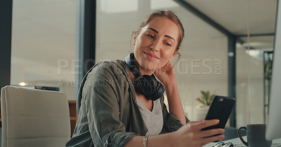 Buy stock photo Shot of a young designer using a cellphone while working in an office