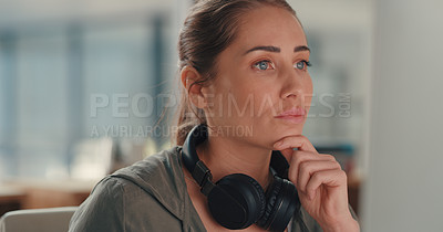 Buy stock photo Shot of a young designer wearing headphones around her neck while working in an office