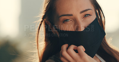Buy stock photo Cropped shot of a young woman wearing a mask while standing outside