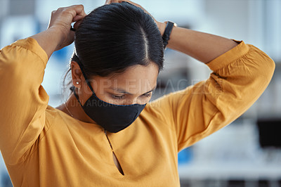 Buy stock photo Shot of a young woman putting on a mask in a modern office