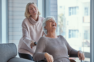 Buy stock photo Shot of a senior woman in a wheelchair sharing a joyful moment with her daughter at home