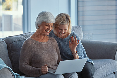 Buy stock photo Shot of a senior woman and her daughter using a laptop to make a video call on the sofa at home