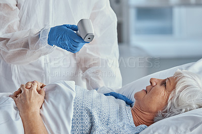 Buy stock photo Shot of a senior woman getting her temperature taken by a doctor in a hospital