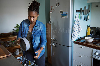 Buy stock photo Cropped shot of a young woman packing dirty dishes in the dishwasher at home