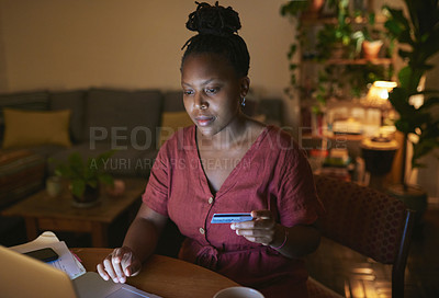 Buy stock photo Shot of a young woman using a laptop and credit card at home at night