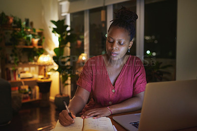 Buy stock photo Shot of a young woman writing notes while using a laptop at home at night