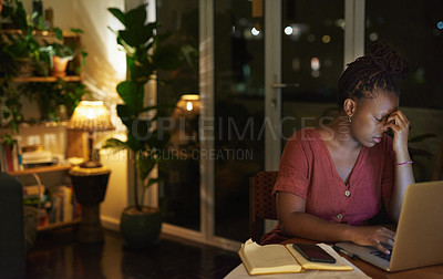 Buy stock photo Shot of a young woman looking stressed out while working on a laptop at home at night