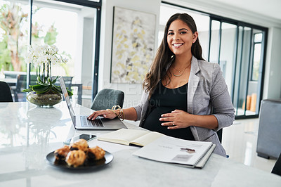 Buy stock photo Portrait of a pregnant young woman using a laptop while working from home