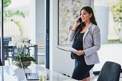 Buy stock photo Shot of a pregnant young woman talking on a cellphone while working from home