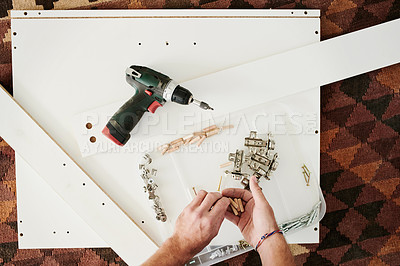 Buy stock photo Cropped shot of a man using a drill to assemble wooden furniture at home