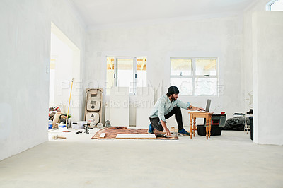 Buy stock photo Shot of a young man using laptop while renovating a house