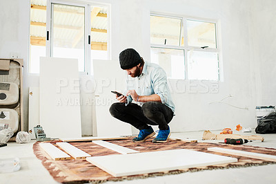 Buy stock photo Shot of a young man using smartphone while renovating a house