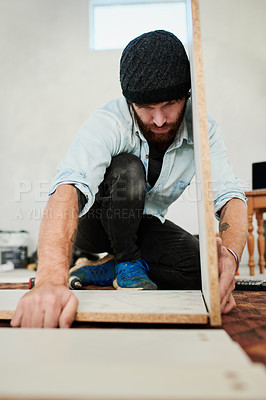 Buy stock photo Shot of a young man assembling a piece of wooden furniture at home