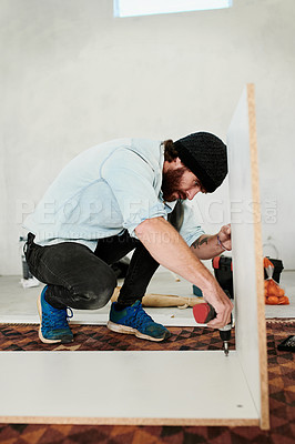 Buy stock photo Shot of a young man using a drill to assemble wooden furniture at home