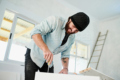 Buy stock photo Shot of a young man using a screwdriver to assemble wooden furniture at home