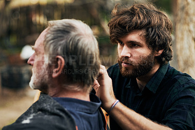 Buy stock photo Cropped shot of an elderly man getting a haircut and beard trim from his son outdoors