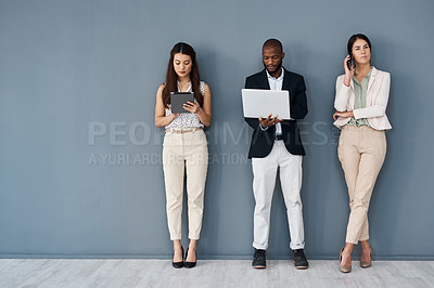 Buy stock photo Shot of a group of businesspeople using digital devices while standing in line against a grey background