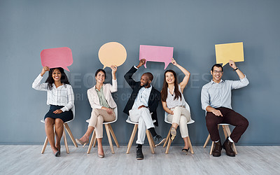Buy stock photo Portrait of a group of businesspeople holding speech bubbles while sitting in line against a grey background
