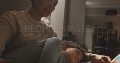 Buy stock photo Shot of a woman reading a book to her daughter at home