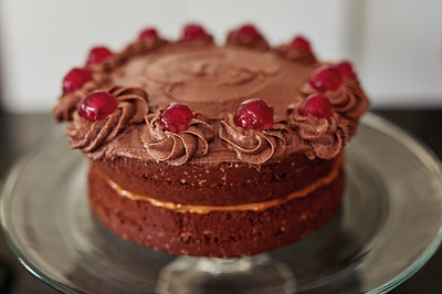 Buy stock photo Shot of a freshly baked chocolate cake with glazed cherries served on a cake stand at home