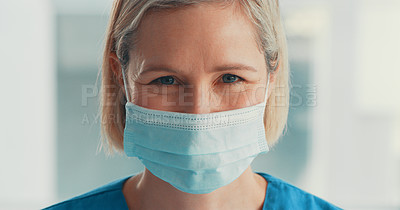 Buy stock photo Portrait of a mature doctor wearing scrubs and a face mask in a hospital