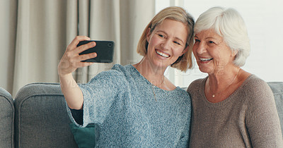 Buy stock photo Shot of a senior woman taking selfies with her daughter at home