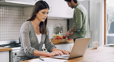 Buy stock photo Shot of a woman sitting with her laptop and paperwork while her husband cooks in the background