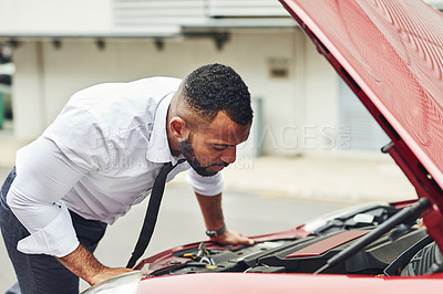 Buy stock photo Shot of a man checking under the hood of his car after breaking down