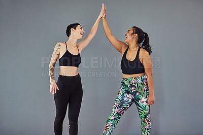Buy stock photo Shot of two young women giving each other a high five after their workout