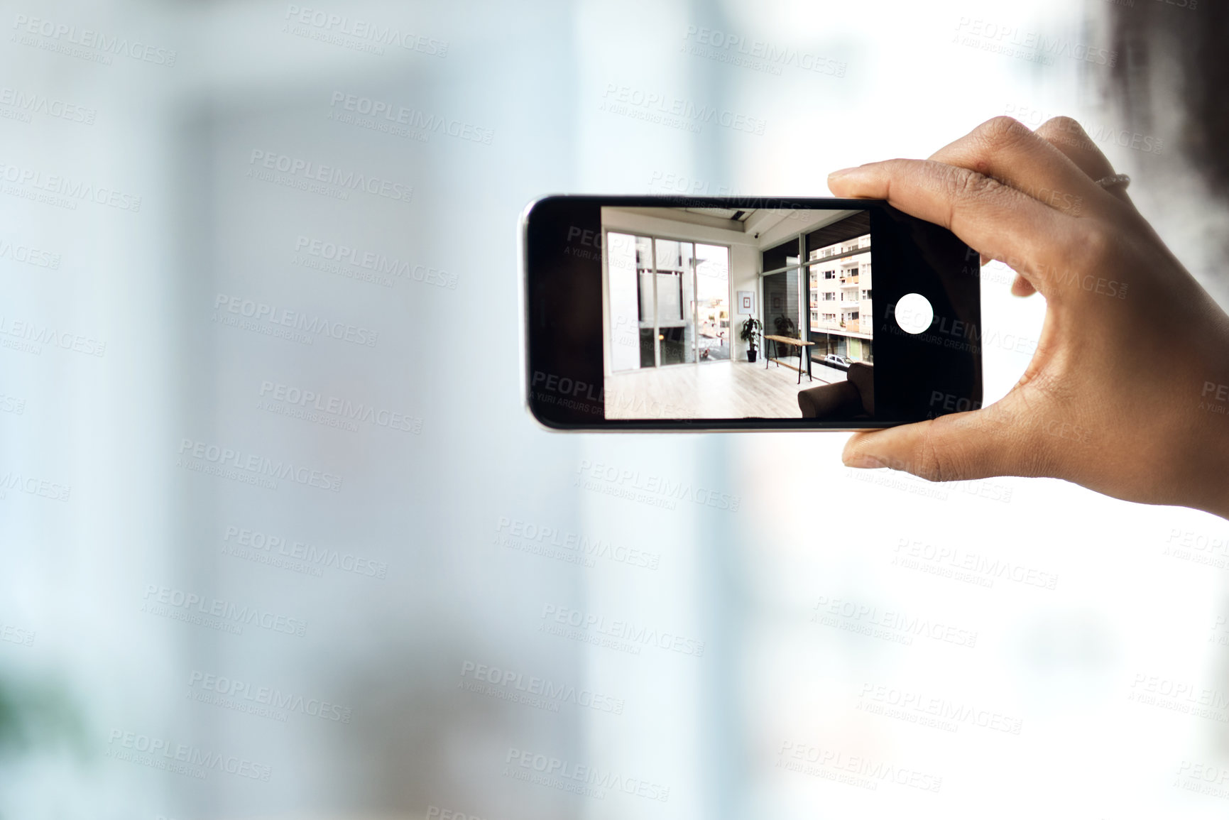 Buy stock photo Cropped shot of an unrecognisable woman photographing the interior of a house with a smartphone
