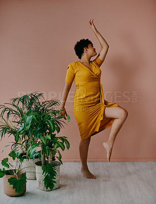 Buy stock photo Shot of a young woman dancing around plants against a brown background