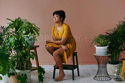 Buy stock photo Shot of a young woman sitting on a stool with plants around her at home