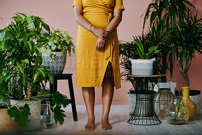 Buy stock photo Closeup shot of an unrecognisable woman standing with plants around her at home