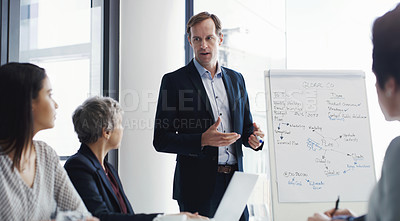 Buy stock photo Shot of a mature businessman giving a presentation to his colleagues in a boardroom