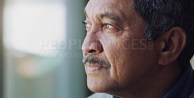 Buy stock photo Shot of a senior man looking thoughtfully out of a window