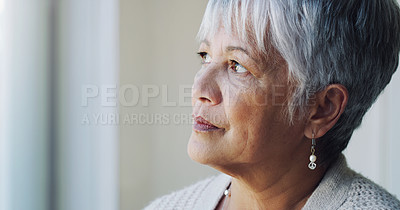 Buy stock photo Shot for a senior woman looking thoughtfully out of a window