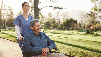 Buy stock photo Shot of a senior man in a wheelchair spending time in the park with his nurse
