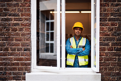 Buy stock photo Shot of a young engineer standing in the window of a construction site