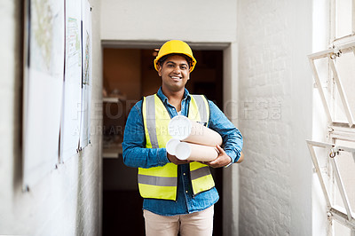Buy stock photo Shot of a young engineer holding blueprints on a construction site