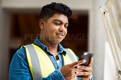 Buy stock photo Shot of a engineer using his cellphone while at work