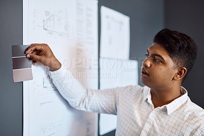 Buy stock photo Shot of a young architect deciding on a colour scheme while working on a project